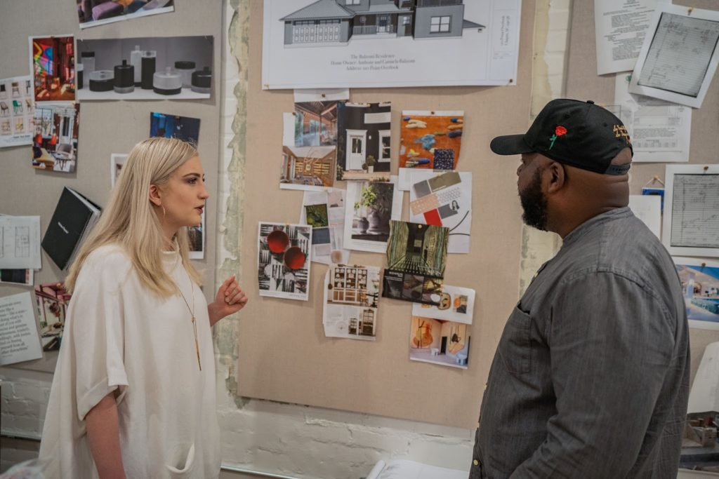Phase one designer showing a customer a wall with pictures of different design elements