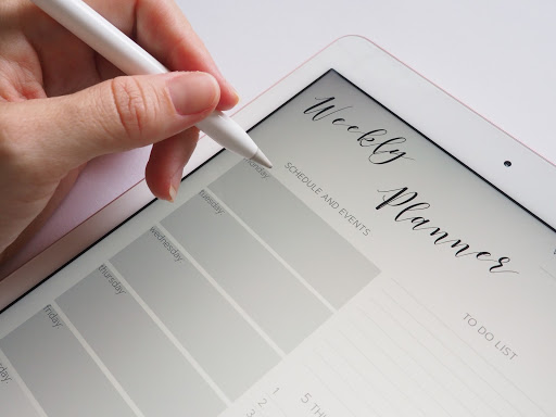 Writing in a weekly planner on a tablet